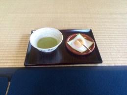 Grüner Tee mit süßem Stückchen anbei