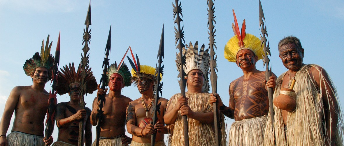 Traditionally garbed and armed with ritual spears, seven Yawanawá men pose for a rare photograph.