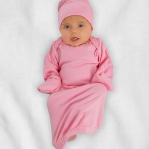 Baby wearing pink layette gown and cap
