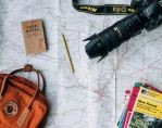 Picture of a map with a camera, notebook, backpack on top. Someone is preparing to travel.