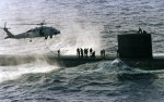 Navy SEALS on top of a submarine with a helicopter above them. Picture for decorative purposes only.