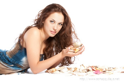 pretty young woman curly hair hold sea shell in hand