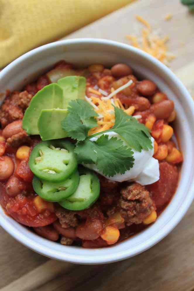 What beats a hot bowl of chili?! This hearty Beef & Corn Chili is the perfect crowd pleaser. It's packed with ground beef, beans, tomatoes, and corn. Garnish with your favorite toppings to make the perfect meal-in-a-bowl. Crockpot, slow cooker, and Instant Pot friendly! | #SoHappyYouLikedIt