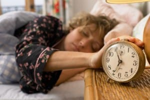 woman-asleep-in-bed-resting-hand-on-alarm-clock