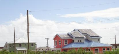 House with solar panels next to house without