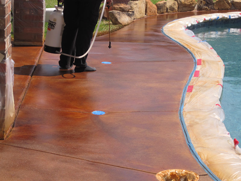 spraying sealer on an acid stained pool deck