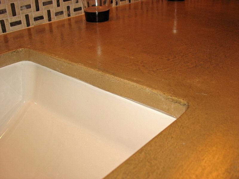 exposed edge of beige concrete countertop in sink area