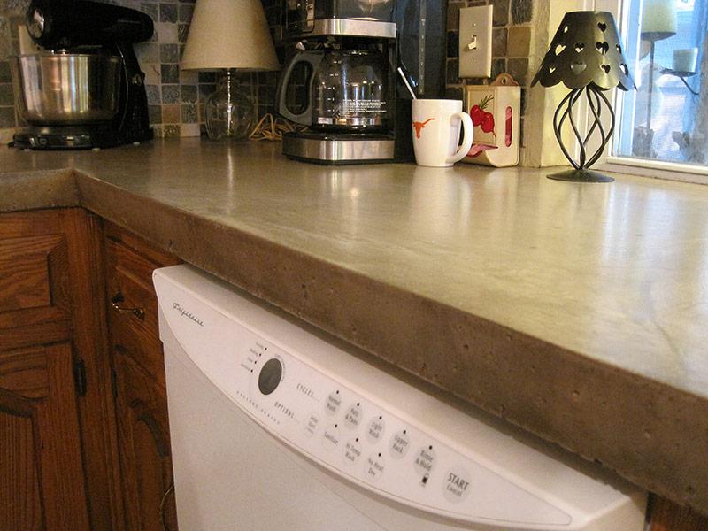 closeup view of dishwasher underneath concrete countertops