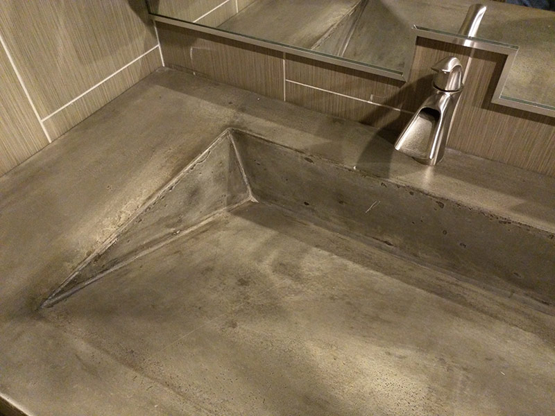 close up of gray concrete ramp style sink