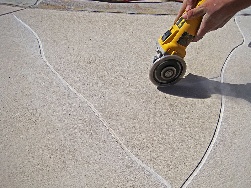 following chalk lines with the right angle grinder to score the floor