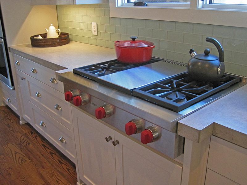 stove top next to light gray concrete countertop