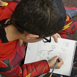 a Sand Point Housing comic book artist in action