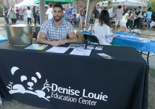Man sits at Denise Louie Education Center's table.