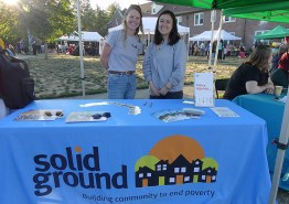Two young women in grey T-shirts stand behind a table with a blue tablecloth and the Solid Ground logo on it
