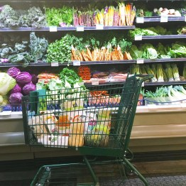 Whole Foods Market shopping cart with groceries in front of a display of veggies