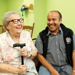 Elderly lady with cane sitting next to Senior Volunteer.