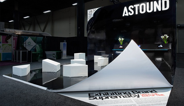Astound exhibition booth featured the flooring seemingly peeling back revealing text that reads 'exhibiting brand supremacy'