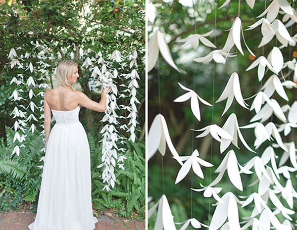 Beautiful wedding white paper craft garland hanging from a tree shaped like lillies