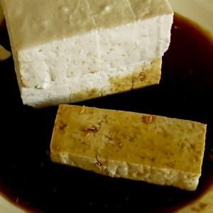 Uncooked tofu on a plate with soy sauce