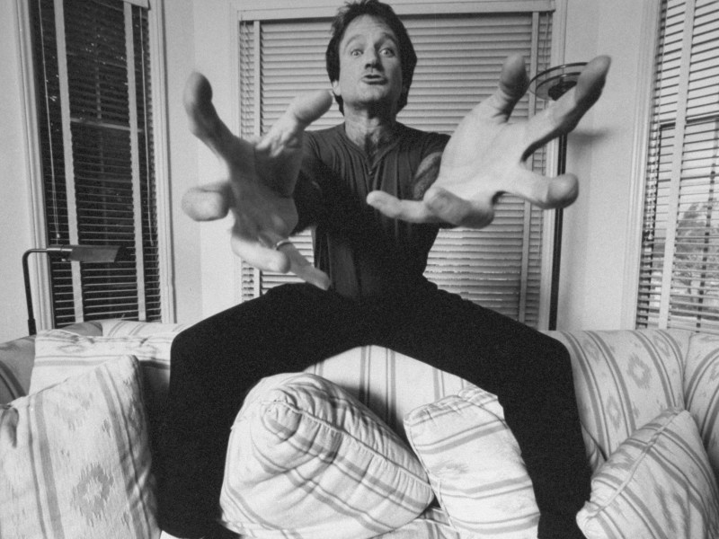 Actor/comedian Robin Williams standing on couch extending his hands at the camera like a crab in Robin Williams: Come Inside My Mind.