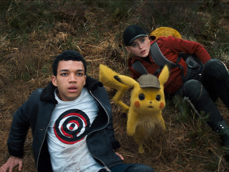 "(L-R) JUSTICE SMITH as Tim Goodman, Detective Pikachu (RYAN REYNOLDS) and KATRHYN NEWTON as Lucy Stevens in Legendary Pictures' and Warner Bros. Pictures' comedy adventure ""POKÉMON DETECTIVE PIKACHU,"" a Warner Bros. Pictures release."