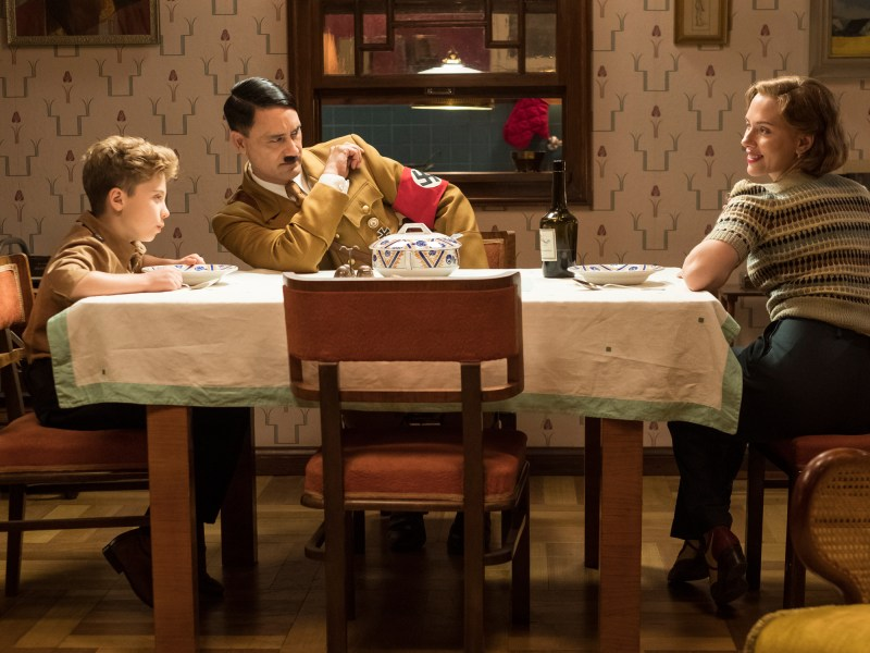 (From L-R): Jojo (Roman Griffin Davis) has dinner with his imaginary friend Adolf (Writer/Director Taika Waititi), and his mother, Rosie (Scarlet Johansson), in Jojo Rabbit
