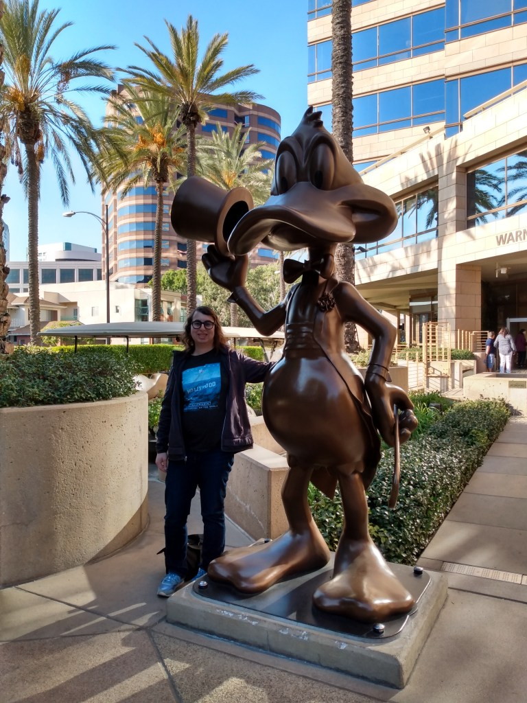Danielle Solzman poses with Daffy Duck in front of the Warner Brothers Studio tour entrance.