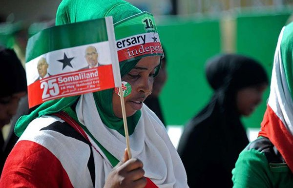 This file photo taken on May 18, 2016 shows a woman holding a flag as soldiers and other military personnel of Somaliland march past during an Independence day celebration parade in the capital Hargeisa. It wants to be recognised as autonomous. PHOTO | MOHAMED ABDIWAHAB | AFP