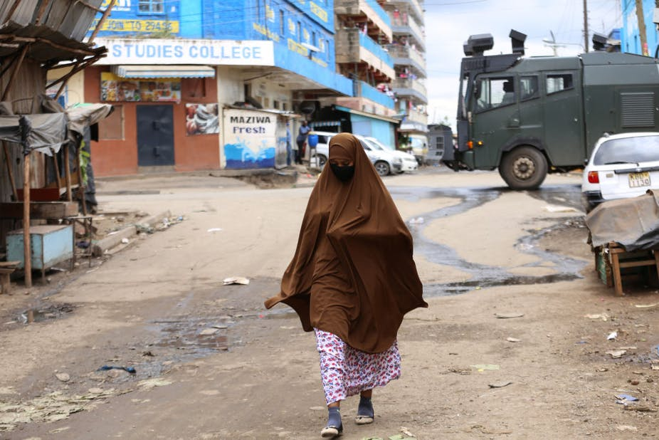 """A woman walks past a police armed vehicle in Eastleigh - Nairobi's """"little Mogadishu"""" Photo by Billy Mutai/SOPA Images/LightRocket via Getty"""