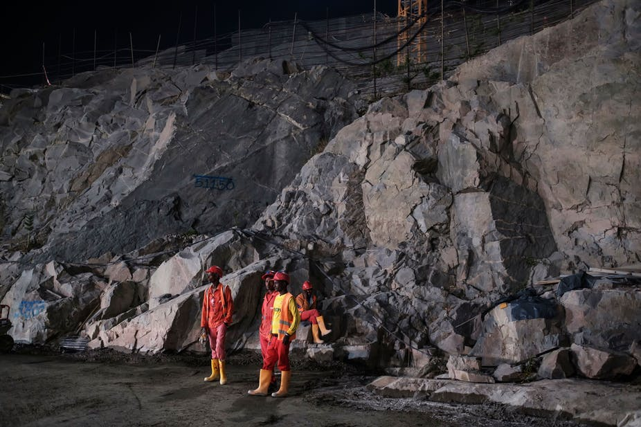 Construction workers stand next to rock wall at the Grand Ethiopian Renaissance Dam in Ethiopia on December 26, 2019.