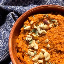 Red hand-made ceramic bowl holding romesco sauce, garnished with crushed hazelnuts and dried parsley.