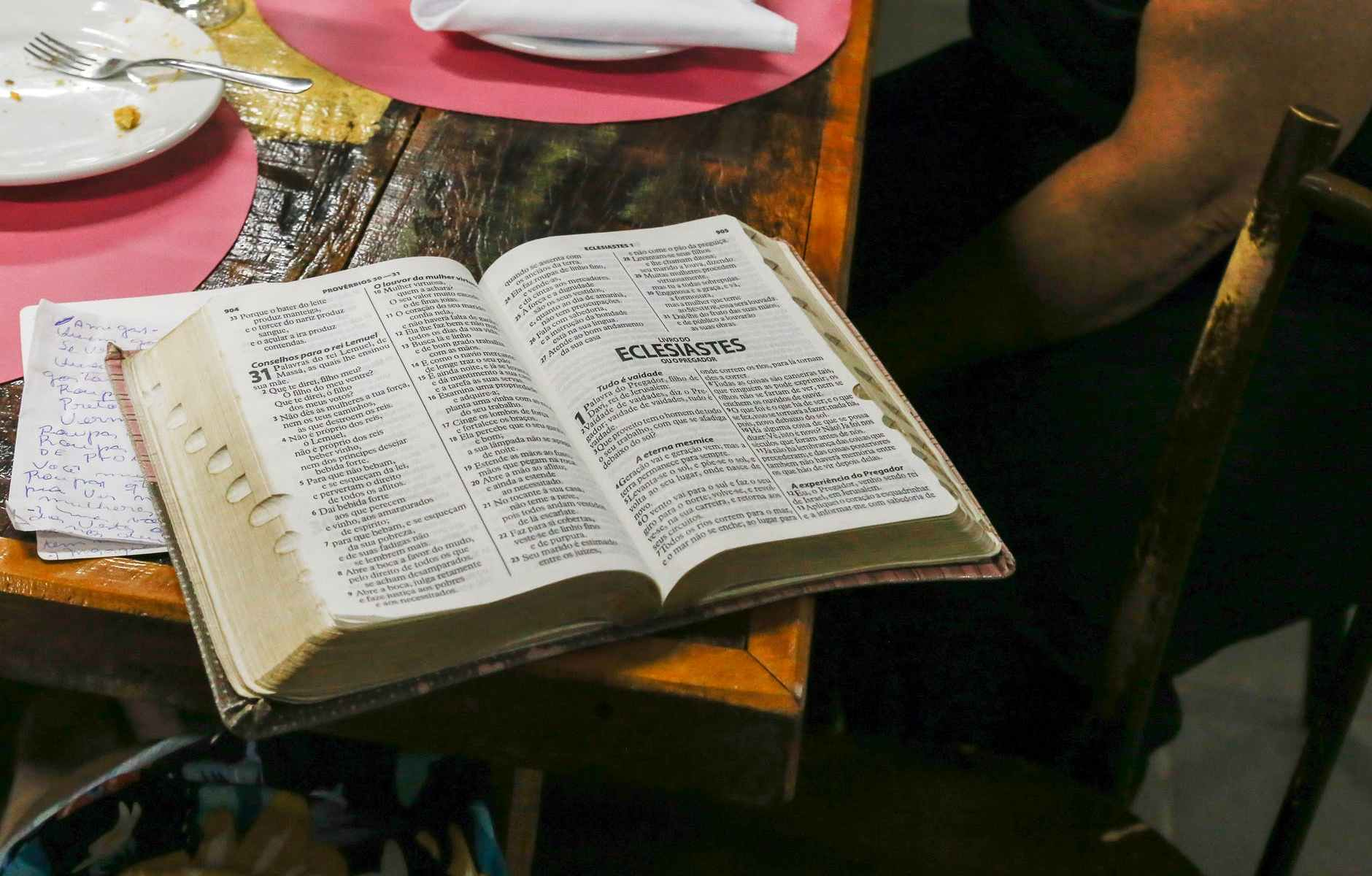 photo of opened bible book on brown table