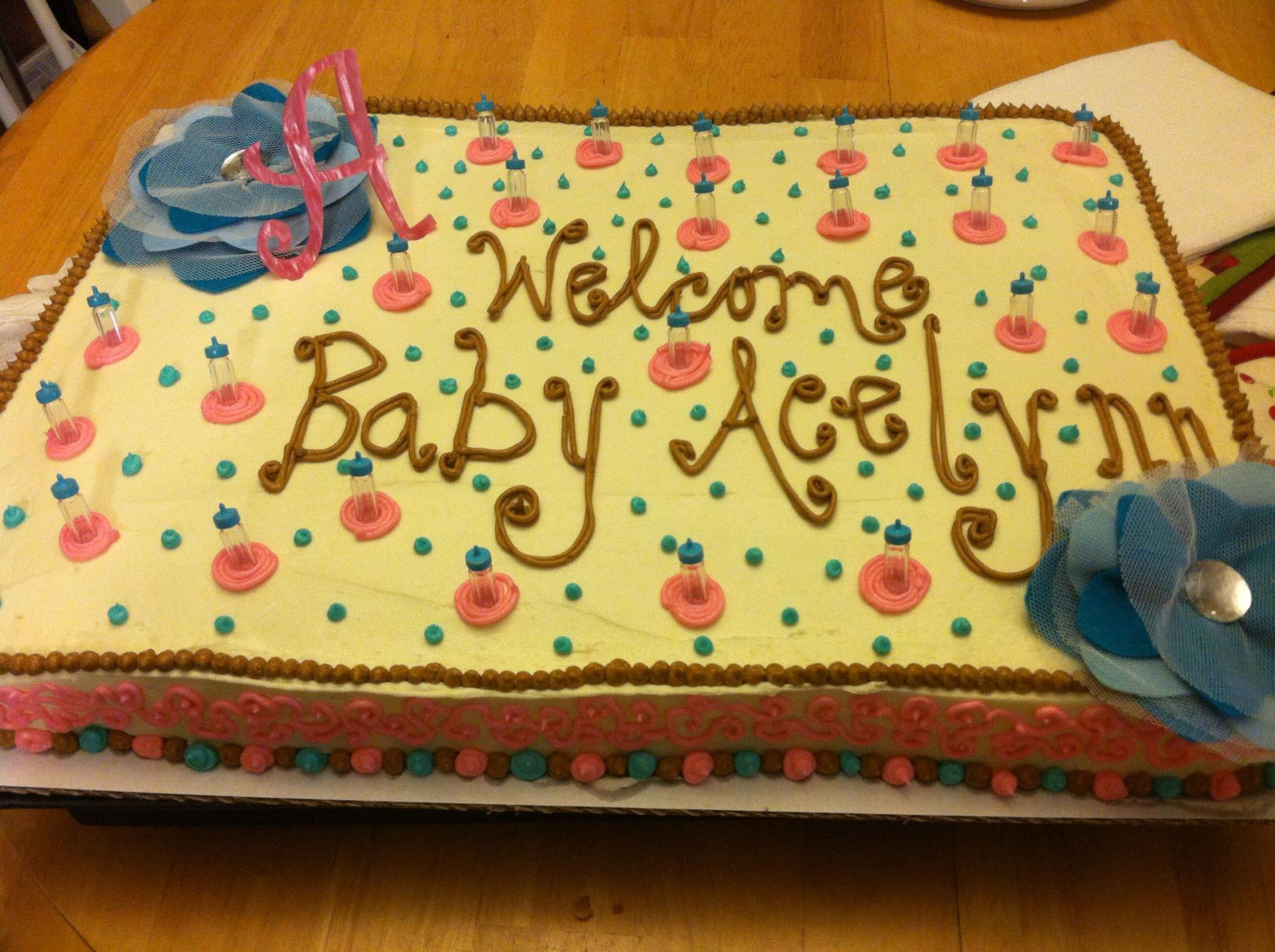 Baby Shower Sheet Cake with Plastic Baby Bottle Decor and Fabric Flowers