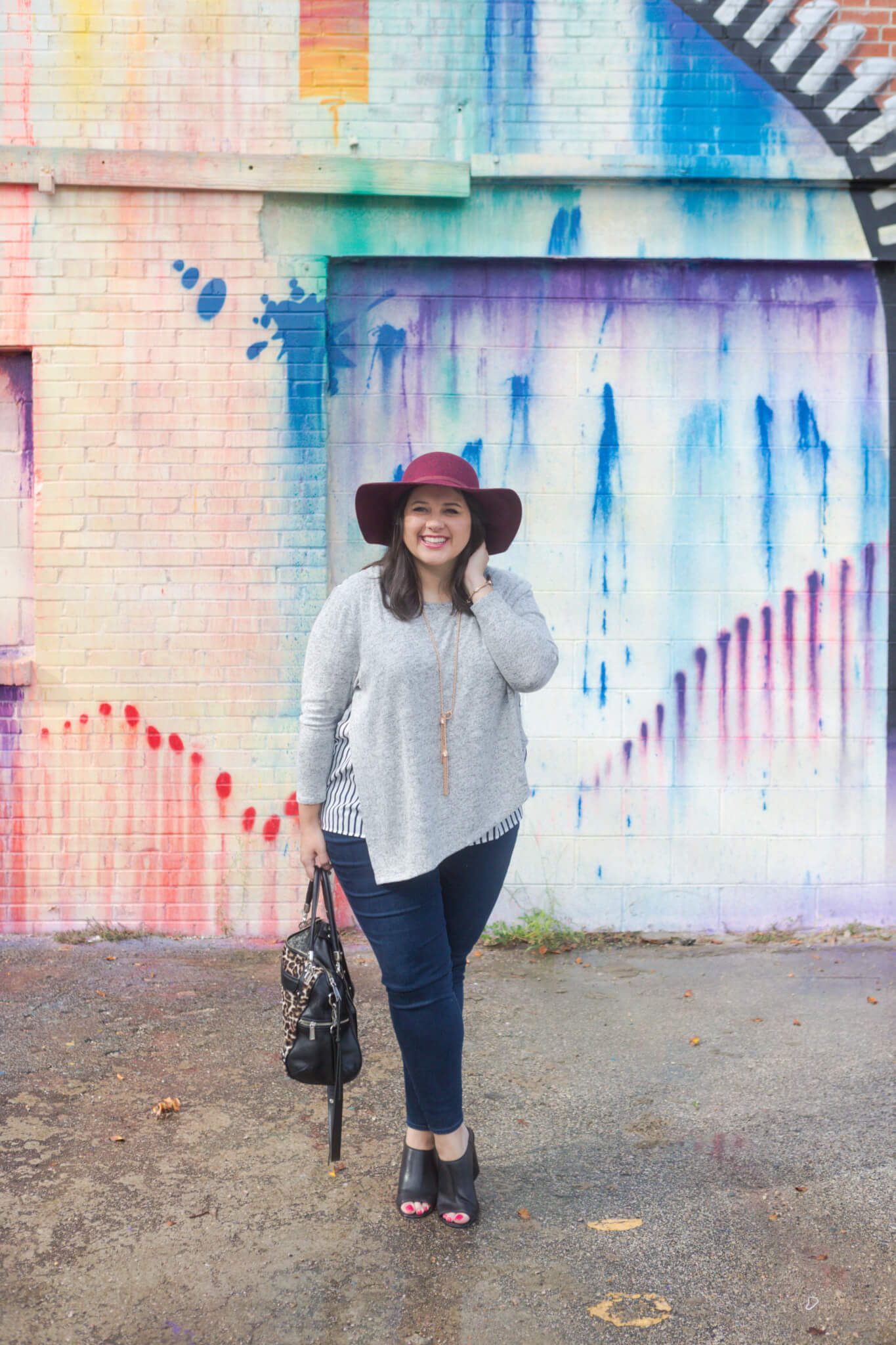 Emily Bastedo from curvy style blog, Something Gold, Something Blue is braving the heat of Houston to share this asymmetrical comfy sweater from Lane Bryant. Paired with my favorite Old Navy maroon hat and a functional leopard bag, tassel Kendra Scott necklace and Cole Haan booties, I am so ready for the fall weather.