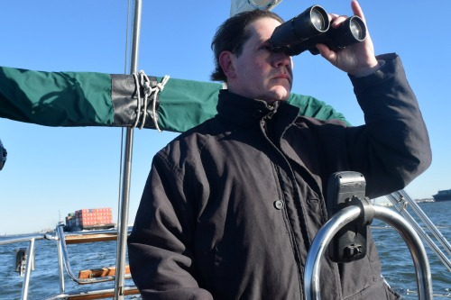 Mike at the helm with a container ship behind.