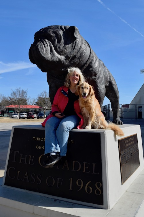 Honey the golden retriever poses with Pam in front of the Citadel bulldog in Charleston.