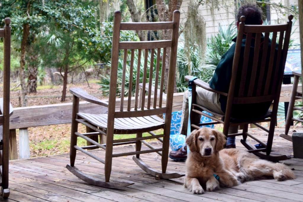 A favorite dog-friendly anchorage on the ICW? Edisto Island State Park. (Golden retriever lying on a porch behind man in a rocking chair.)