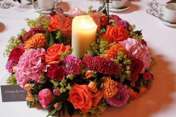 Bright and vibrant ring of flowers with candle