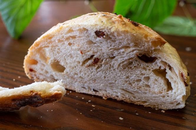 Pane bianco al burro decorato con erbe aromatiche e pomodori secchi