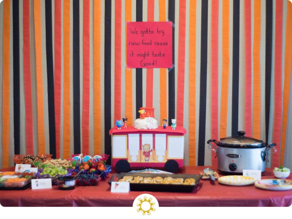 Food for a Daniel Tiger birthday party on a table with red, orange, and black streamers behind (with logo overlay)