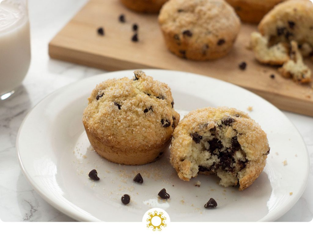 Two chocolate chip muffins, one with a bite missing, on a round white plate with a few extra chocolate chips with a bamboo tray of chocolate chip muffins behind it all on a white and grey marble surface (with logo overlay)