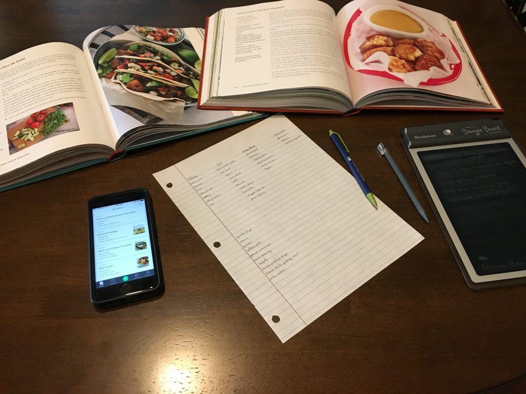Two cookbooks, a cell phone, a piece of paper with a grocery list, and an LED tablet all on a wooden surface