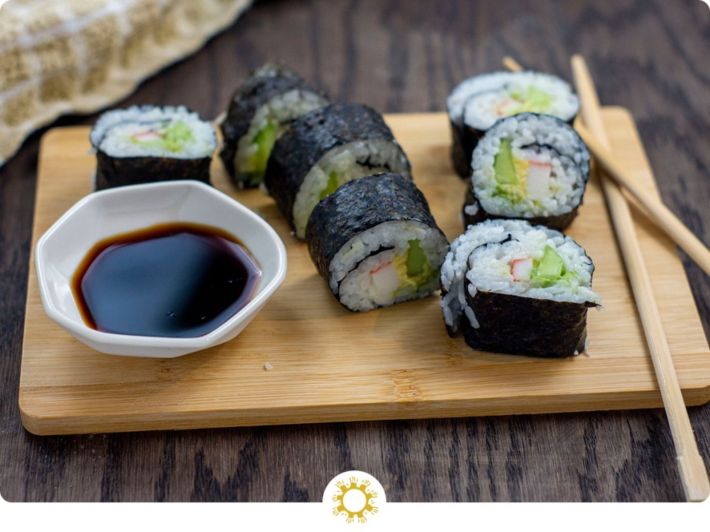 California Roll next to bamboo chopsticks and a white bowl of soy sauce on a bamboo cutting board with a tan and white towel behind all on a wooden surface (with logo overlay)