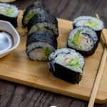 California Roll next to bamboo chopsticks and a white bowl of soy sauce on a bamboo cutting board with a tan and white towel behind all on a wooden surface (vertical with title overlay)