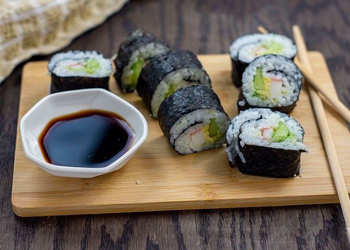 California Roll next to bamboo chopsticks and a white bowl of soy sauce on a bamboo cutting board with a tan and white towel behind all on a wooden surface