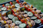 Summer Basil Chicken and Shrimp Kabobs on a metal sheet pan with grass in the background
