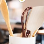 Shallow focus of cooking utensils in a white canister in a kitchen (vertical with title overlay)