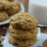 Three oatmeal raisin cookies stacked on pieces of parchment paper with oats and raisins around them with a plate of cookies and a glass of milk behind all on a wooden surface (vertical with title overlay)