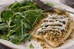 Dijon-Herb Tilapia close up on a white plate with a salad next to it