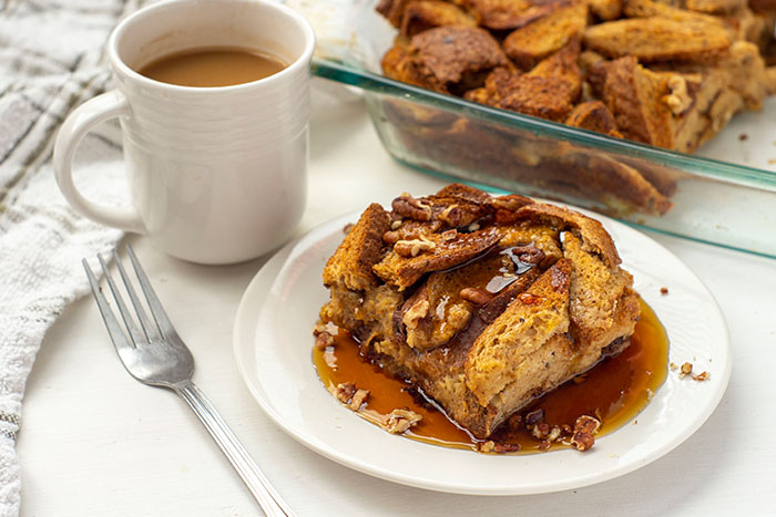 French Toast Casserole topped with chopped pecans and maple syrup on a round white plate next to a fork and a white cup of coffee with the dish of remaining casserole and a white towel in the background all on a white surface